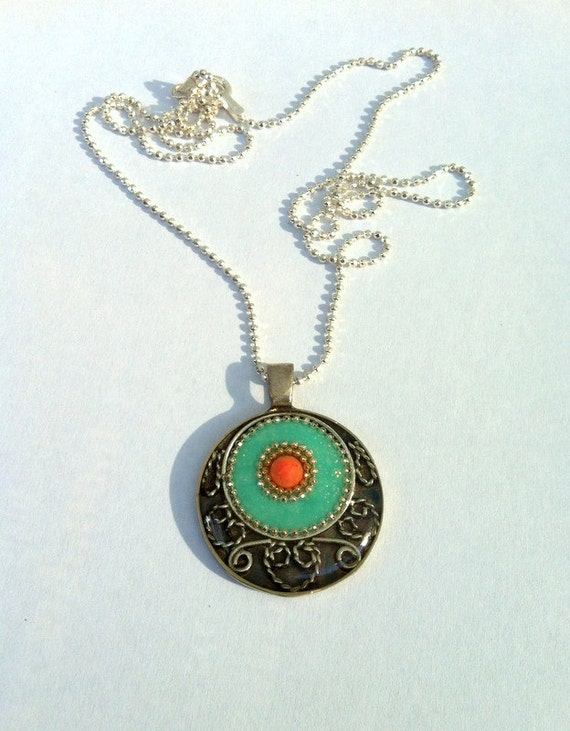 Orange green pendant , sterling silver pendant  made with an inner green circle inlaid with coral stone and an outer black and silver circle