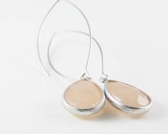 Pastel Peach Teardrop Glass Earrings With A Shiny Silver Tone Frame