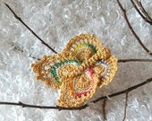 Crocheted butterfly in gold and touches of color