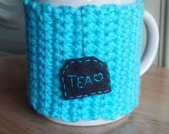 Crocheted tea mug cozy cup cozy in aqua blue aruba sea blue turquoise with hanging brown tea patch