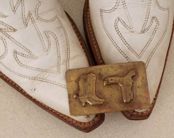 Vintage Western belt buckle with cowboy boots and gun in holster