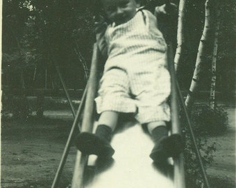 Sliding Board Ride Hanging On For Photo Little Boy in Striped Overalls 1940s Park Playground Vintage Black and White Photo Photograph