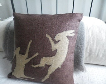 handprinted deep heather tumbling hares cushion cover