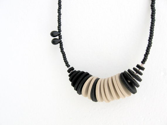 asymmetric chic necklace with beige and black circles and beads