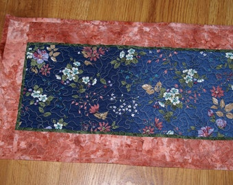 Quilted Table Runner made from a blue floral fabric with peach, lavender and white flowers.