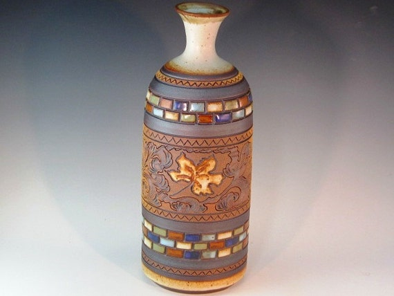 Large Bottle Form Vase With Colored Rectangles And Maple Leaf Carved In Center With Swirl Design