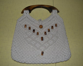 Cream colored macrame purse with wooden handles and bead detail