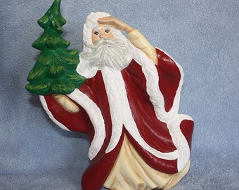 Handpainted ceramic Santa Claus who decked out in the traditional Santa attire and holding a Christmas tree