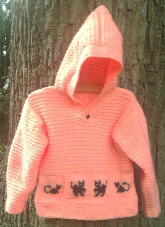 Child's handknit orange sweater hoodie with black cat motifs.