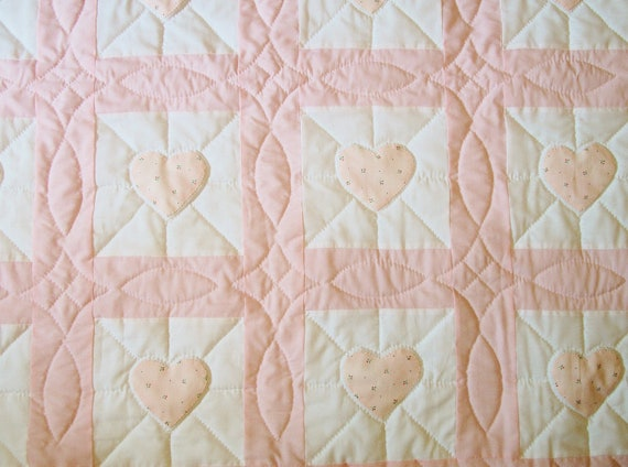Pink baby quilt with hand-appliqued hearts, hand-quilted
