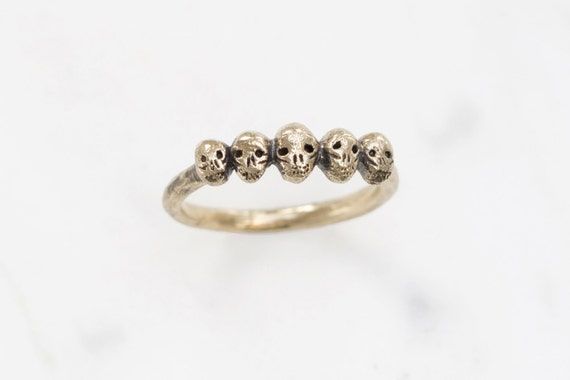 Golden row of tiny skulls ring