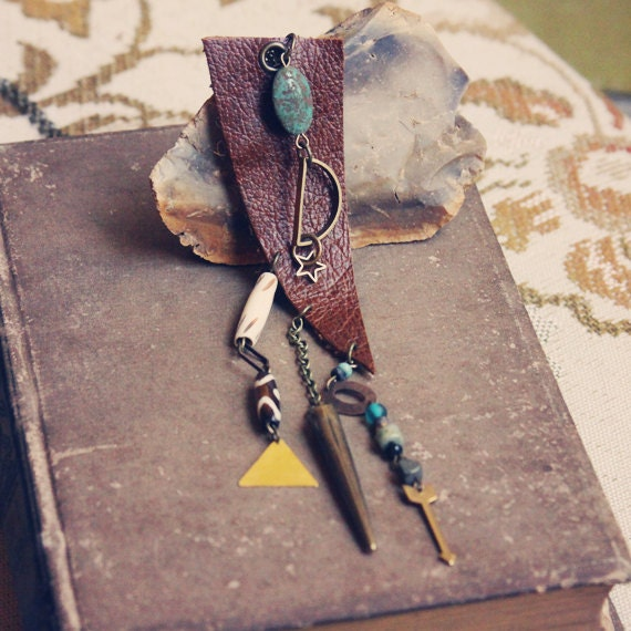 sera. an earthy leather necklace with beads and brass charms.