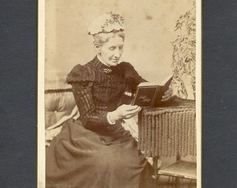 Cabinet Card of an Elderly Woman Looking at a Photo Album Upside Down