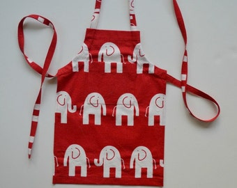Children's apron in red and white elephant print.  Sturdy cotton duck fabric.  Pocket on bib, adjustable ties.  Sizes 1-6.