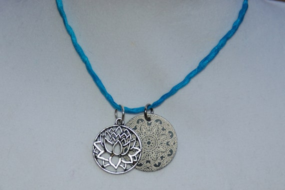 Necklace lotus flower and black and silver mandala medallion on hand dyed blue silk chord