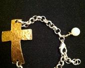 Gold sideways cross bracelet on silver rolo chain