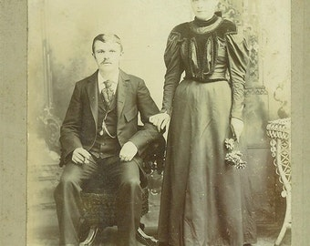 Victorian Husband And Wife Wearing Black Dress Velvet Top Holding Flowers Standing  Antique Photo Cabinet Card Portrait Studio Photograph