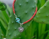 red bracelet with red skull and heart charm