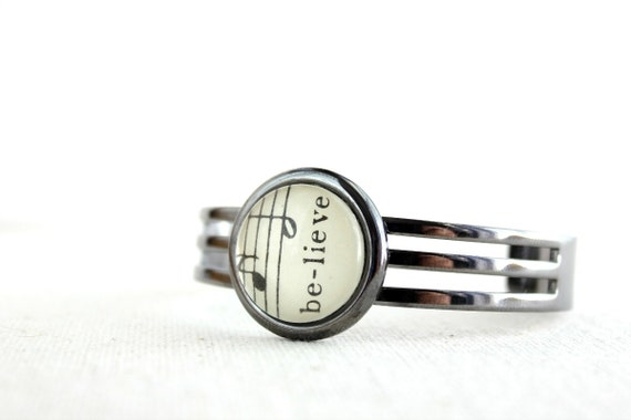 Unisex cuff bracelet for man or woman in shiny gunmetal black adjustable made with vintage sheet music uplifting word believe