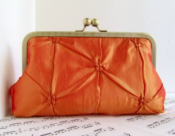Pinched taffeta tangerine orange clutch bag in frame
