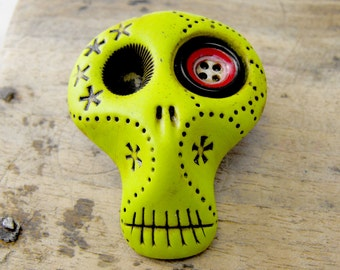 Sugar skull in lime tone green with a cute button in his eye. Brooch, keychain, pendant or magnet (you choose)