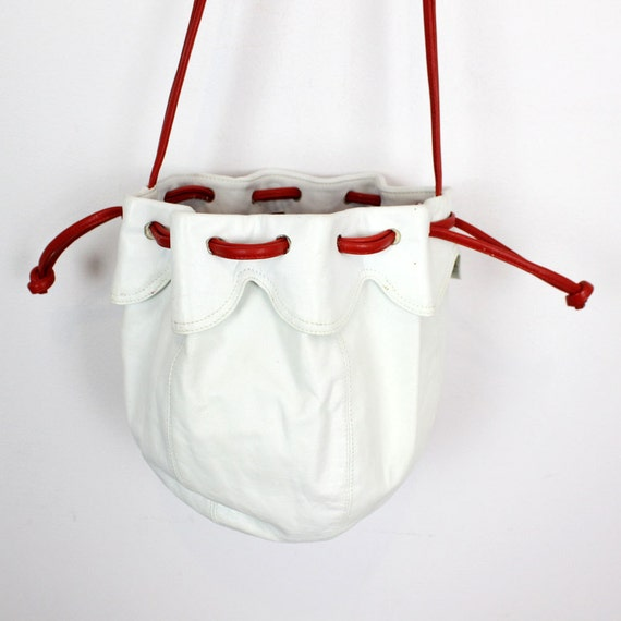 white leather cinch bag / red trim cross body bucket bag