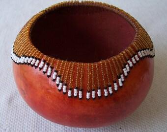 Medium dark rust orange gourd bowl, beaded wavy rim pattern. 941.