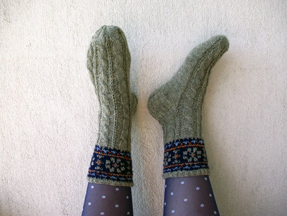 Hand knitted cabled wool socks with ornament.