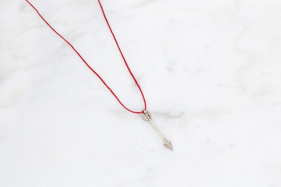 Silver arrow pendant on red silk cord