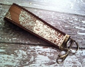 Brown with muted pastel medallions print key fob wristlet on brown cotton webbing with swivel lobster clasp