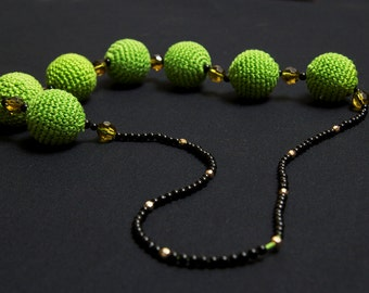 Necklace with crochet green balls, black, blue and silver beads