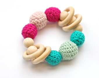 Pink and green teething toy with 4 wooden rings.