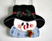 Snowman with blue scarf, pine and holly berries, candy cane nose