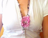 Vintage-style antique gold necklace with pink crochet work, charm, and beads