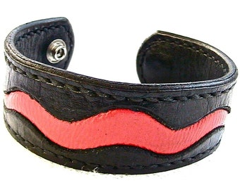 Black leather cuff bracelet with red leather inlay.