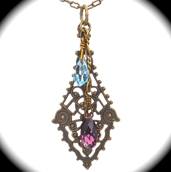 Gorgeous filigree pendant with antiqued bail and amethyst Swarovski briolette and crystal on 20 inch antiqued brass chain.