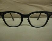 Horned Rimmed Mad Men Era Eyeglasses Sunglasses Black frames with prescription lenses and metal detailing at temples