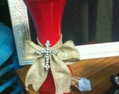 Red vase with burlap bow and bling cross