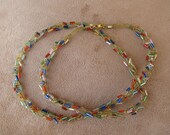 Gold tone wire with multi colored tube beads. 23 inch length.
