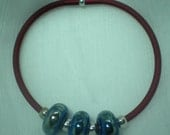 3 beautiful lampwork glass blue beads with silver mirrored spots  on a dark red rubber tubed bracelet with fastener