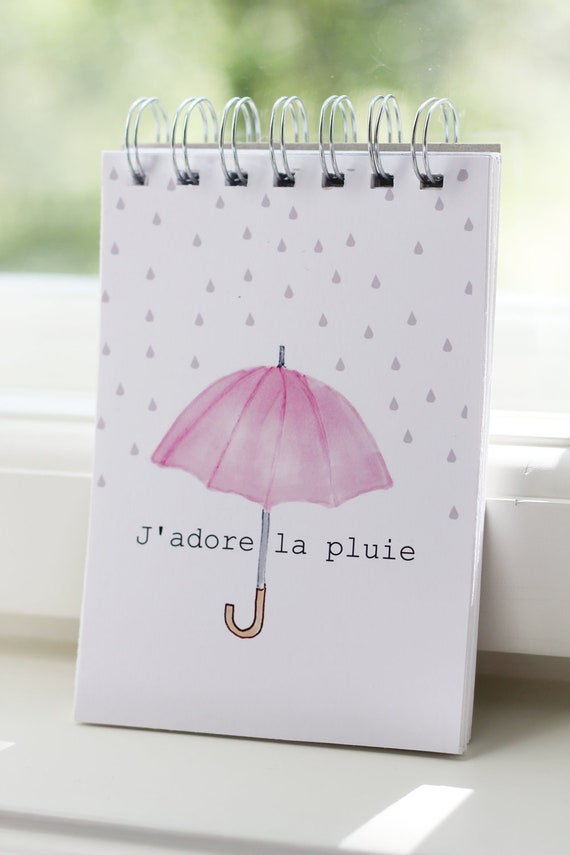 Notebook with a pink umbrella and raindrops