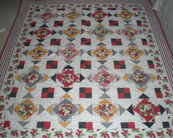 Quilt in bright red, green, yellow, black and cherry fabrics.