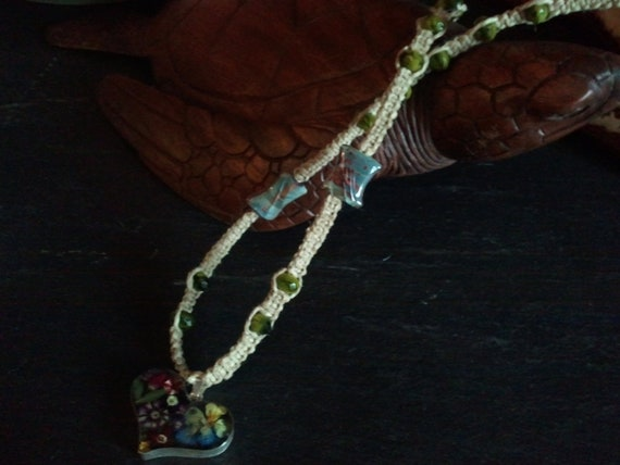 dried flowers in resin twisted on 20lb test hemp with 2 hand blown glass  beads and  green czech glass beads to accent  the piece