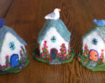 Needle felted cottage with its own garden and a bird on the roof