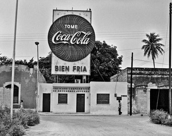 Two passersby ignore huge Coca Cola sign in Merida in Mexico- a black and white photograph
