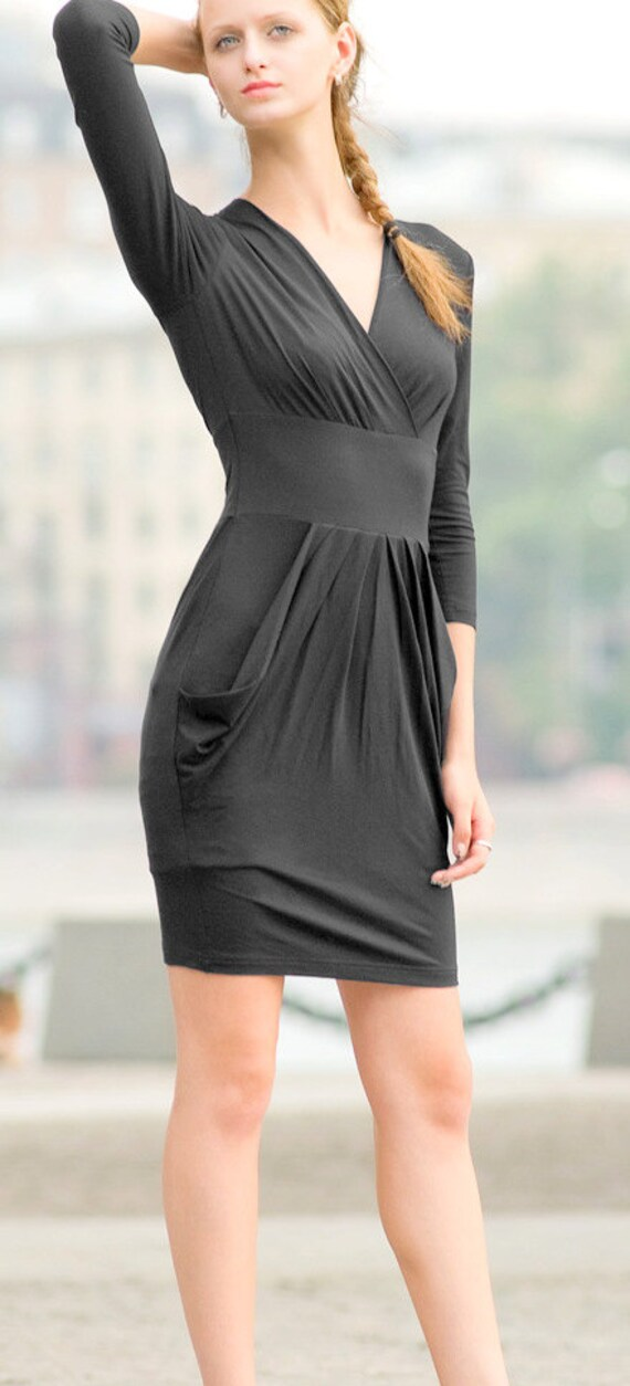 black dress with long sleeves and draped at the waist. dress with pockets