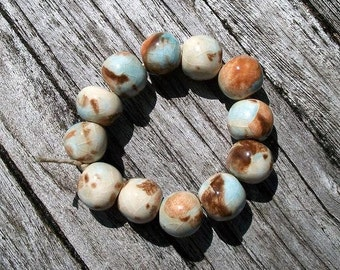 A strand of 12 multi color ceramic round beads in brown and blue
