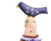 Handmade textile cloth art doll with bird on top of her head