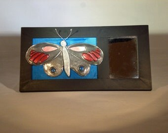 Repujado (metal embossed) butterfly with mother of pearl inlay on a framed mirror