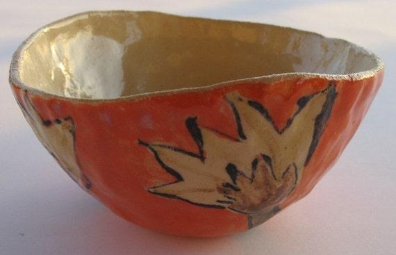 Orange ceramic bowl with painted flowers